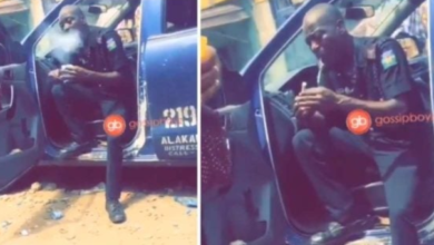 Photo of Nigerian Police Officer seen rolling up something that looks like Marijuana